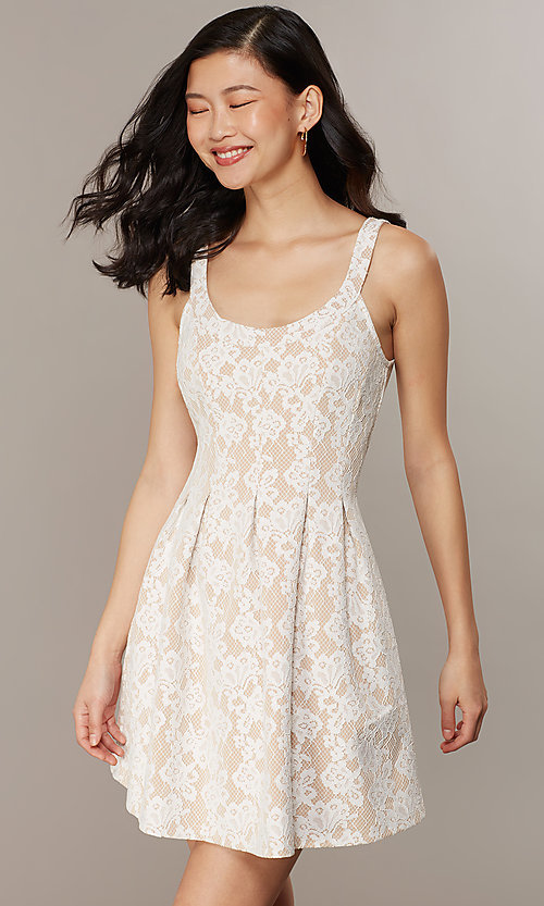 Image of short white lace graduation dress with pockets. Style: CHE-D16131CYN Detail Image 1